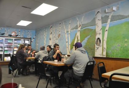 A creative mural covers the entire interior wall of the restaurant