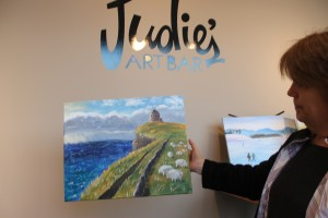 Owner Katie Day displays one of her recent paintings.