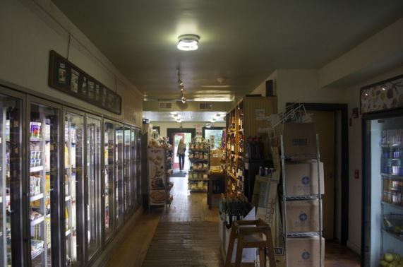 This hallway, filled with refrigerated goods such as beer and a wine collection on the right, connects the market and the café.